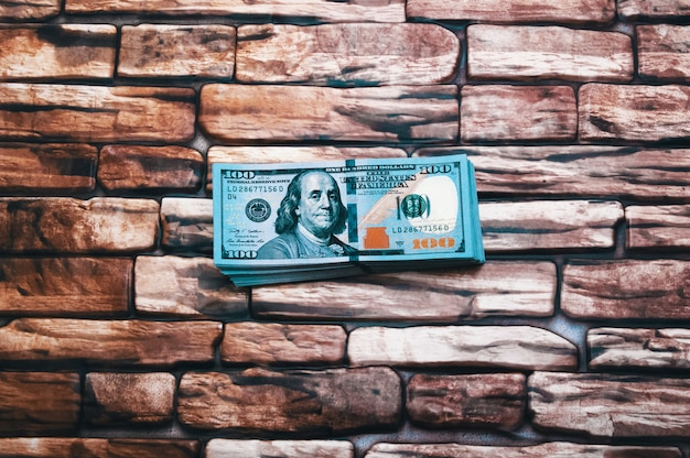 ドルのパック。濃い赤茶色のレンガの壁に100ドル札の大きな塊が横たわっています。