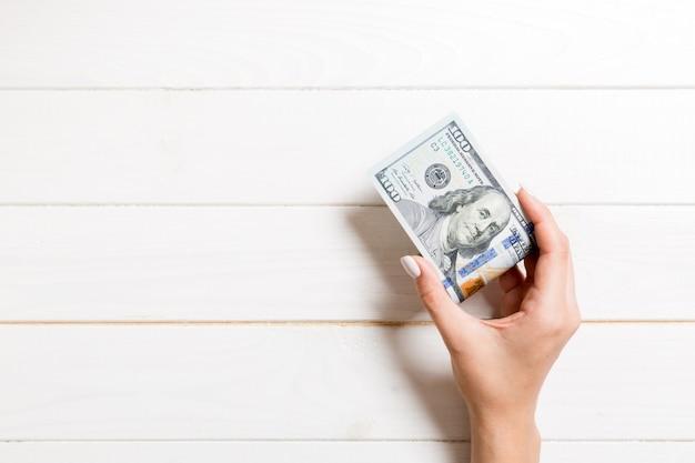 Пакет 100 долларовых банкнот в женской руке на деревянном. концепция зарплаты с копией пространства