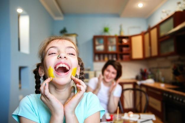 땋은 머리를 가진 페인트 얼룩진 소녀가 집에서 부엌에서 웃고 있습니다.