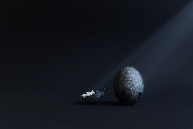 Раскрашенное темное пасхальное яйцо стоит на столе в тонком луче света