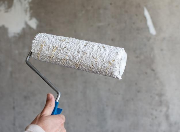 화가는 콘크리트 벽을 흰색 페인트로 칠하고, 남자 손은 벽을 칠하기 위한 페인트 롤러로 칠한다
