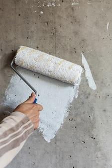 Художник красит бетонную стену белой краской, мужская рука малярным валиком для покраски стены.