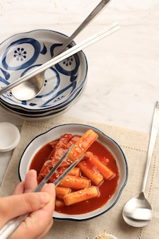 한 쌍의 젓가락으로 그릇에 담긴 떡볶이, 한국에서 인기 있는 길거리 음식