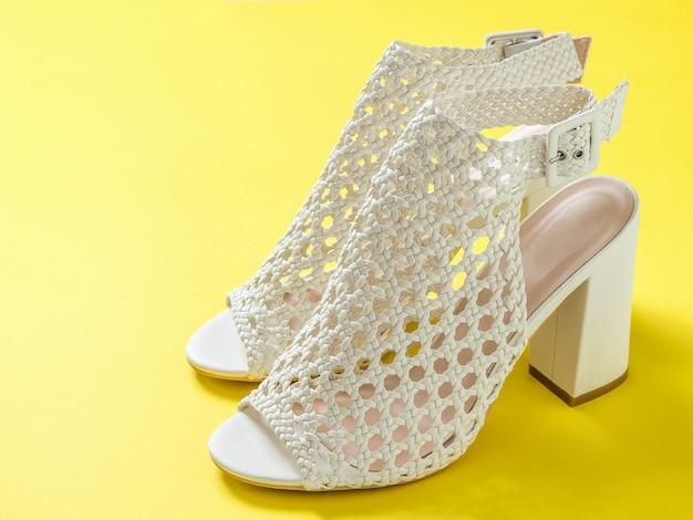 黄色の背景に美しい女性の夏の靴のペア。女性のための夏の靴。