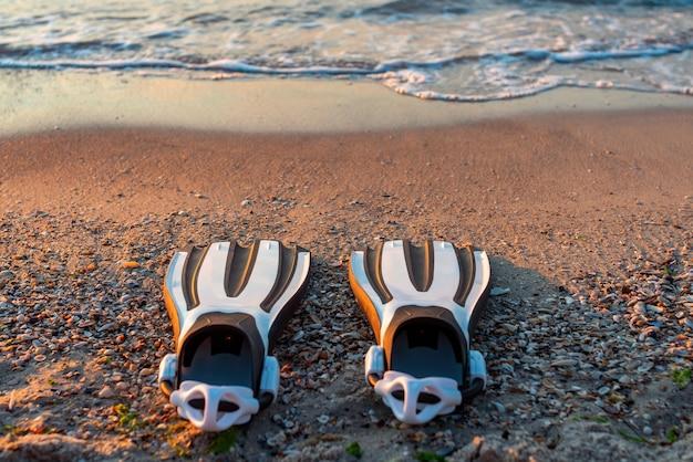 ビーチの砂の上にある黒と白のスキューバフィンのペア