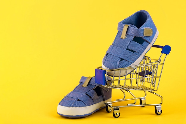 Пара синих детских сандалий, кроссовок на тележке на желтом