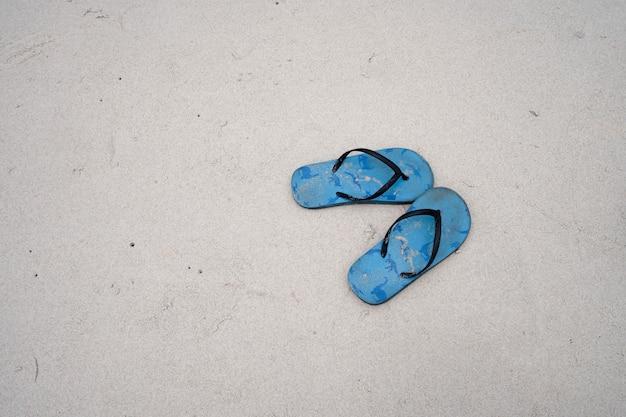 하얀 모래 해변에 있는 파란색 고무 슬리퍼 한 켤레, 고운 거친 모래 질감, 위쪽 전망 및 복사 공간