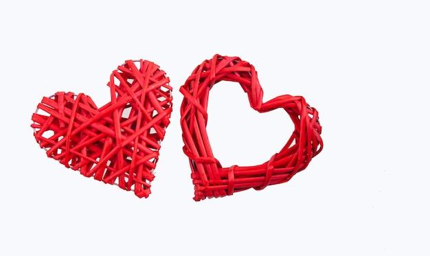 Пара плетеных красных сердечек на белом фоне. концепция праздника