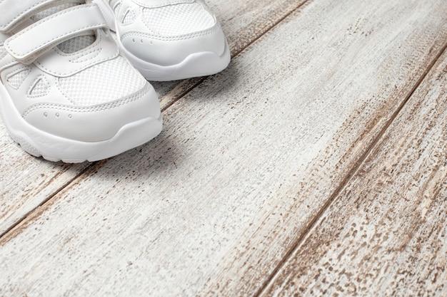 Пара детских кожаных спортивных кроссовок сшитой из ткани с застежкой-липучкой с обувью ...