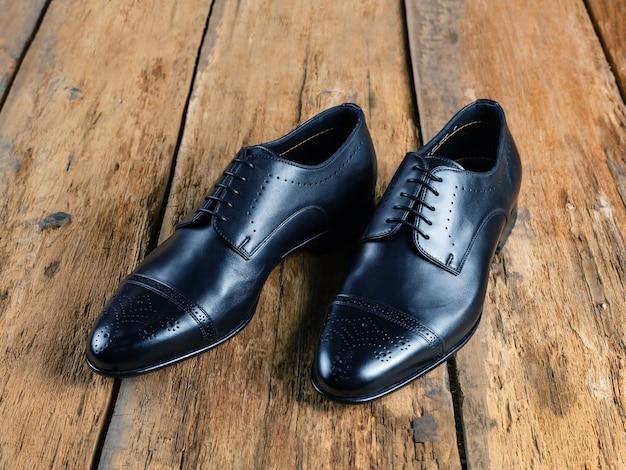 古典的な黒い革の靴のペアは、古いボード、側面図にあります。閉じる。セレクティブフォーカス