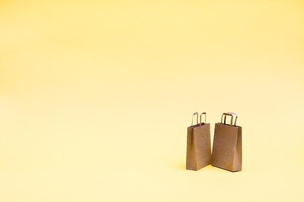 黄色の背景に環境に優しいクラフト紙の買い物袋のペア。ブラックフライデーギフトの販売。コピースペース