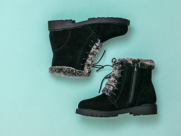Пара модных женских черных туфель на синем фоне. модные стильные женские зимние сапоги. плоская планировка.