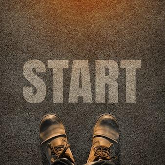スタート地点の概念のために、スタートという言葉の白いプリントが付いた舗装道路の足のペア。