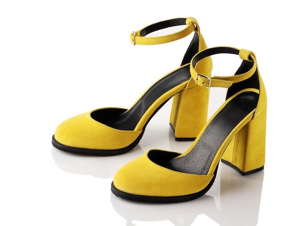 Пара женских желтых замшевых туфель на высоком каблуке на белом фоне.