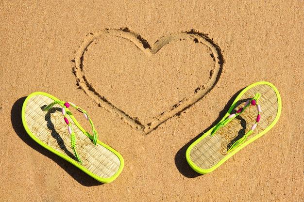 ハート型の砂の中のビーチサンダル