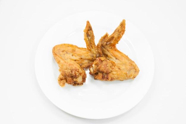 Пара жареных куриных крылышек на белом блюде