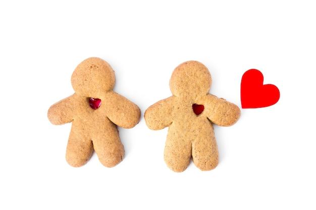 白い背景で隔離の心を持つジンジャーブレッド愛好家のペア。愛を込めてクリスマスクッキー。テキストの場所。高品質の写真
