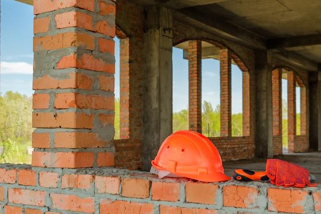 Пара перчаток и шлем масона на стройке дома из красного кирпича.