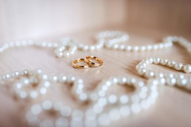 Пара золотых обручальных колец на фоне белого жемчуга. крупный план.