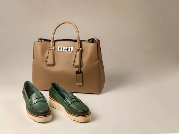 靴底が厚い緑色の婦人靴。近くには淡い色の女性用レザーバッグがあります。明るい背景の側面図。スペースを右側にコピーします