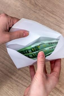 봉투에 돈을 들고 한 쌍의 손