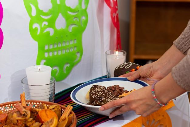 メキシコの家で典型的なメキシコの死者の日を捧げる典型的なメキシコの死者の日料理を置く一対の手