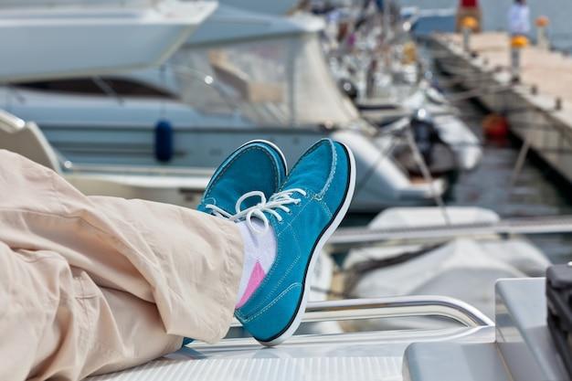 Пара человеческих ног в штанах и ярко-синие топсайдеры на фоне палубы яхты. яхтинг