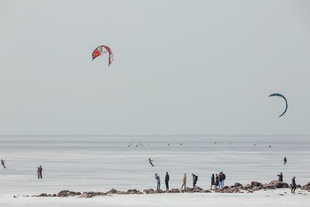 フィンランド湾の海岸を滑空するカイトセーラーのペア