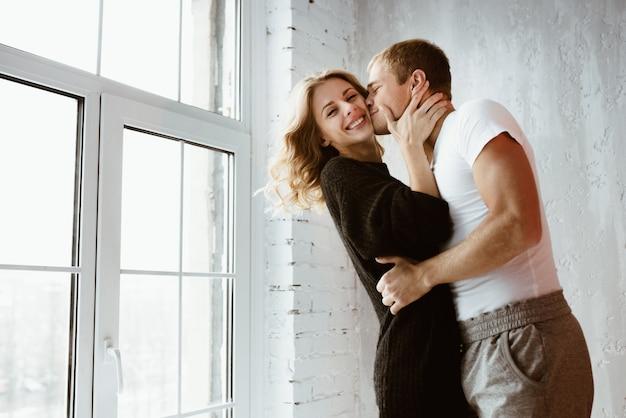 Пара влюбленных, обнимаю, целую, смеюсь. девушка в длинном черном свитере и белом высоком гольфе. салон светло-серый, большое окно, коричневое стильное кресло.