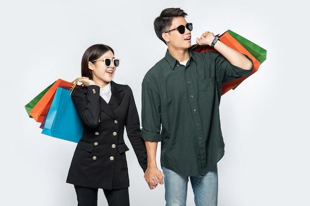 Пара мужчина и женщина в очках несли много бумажных пакетов для покупок