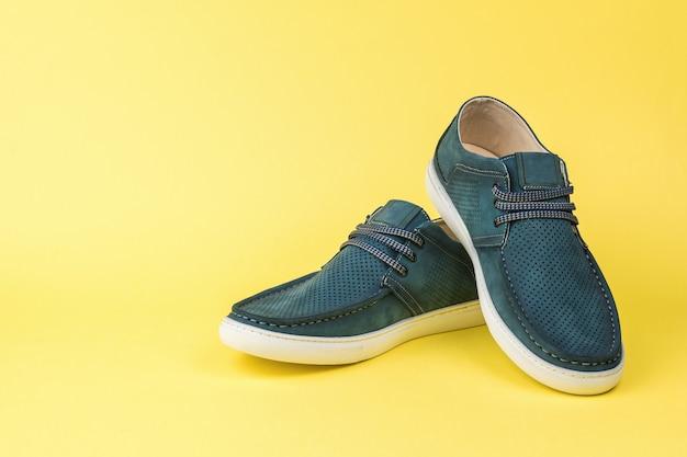 노란색 배경에 남자의 파란색 여름 신발 한 켤레. 편안한 여름 남성 신발.