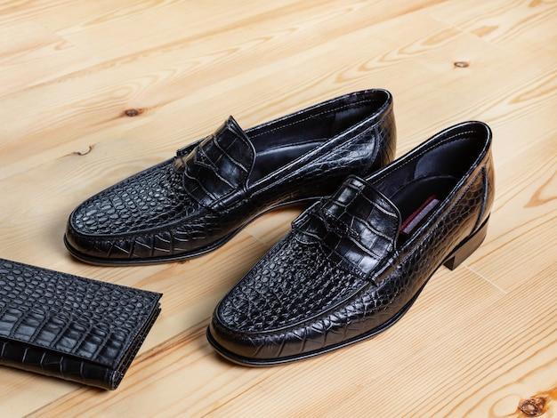 淡い色の板でできた木の表面に、紳士靴とクロコダイルレザーの財布が横たわっています。