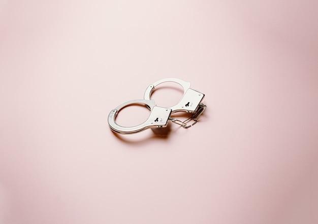 平らで明るいパステルピンクの背景の上に金属製の手錠のペア