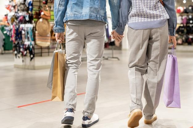 ショッピングバッグを持ってモールを歩いているカジュアルウェアのペア