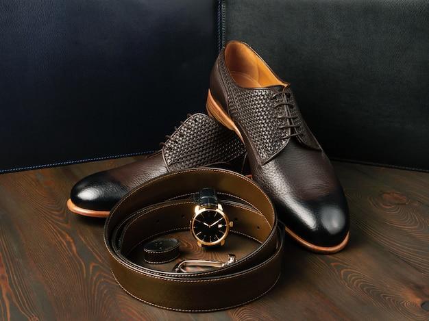 Пара стильных кожаных туфель рядом с коричневым кожаным ремнем, вид сбоку, крупный план.
