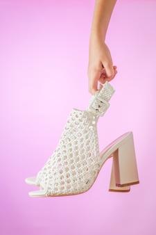 ピンクの背景に手に夏の女性の靴のペア。女性のための夏の革靴。
