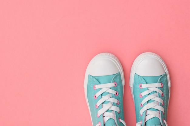 분홍색 배경에 청록색 운동화 한 켤레. . 스포츠 스타일. 평평하다. 상단에서보기.