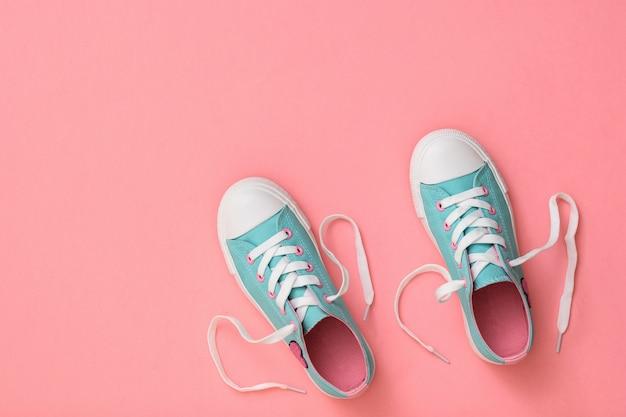 분홍색 바탕에 끈이있는 청록색 운동화 한 켤레. . 스포츠 스타일. 평평하다. 상단에서보기.