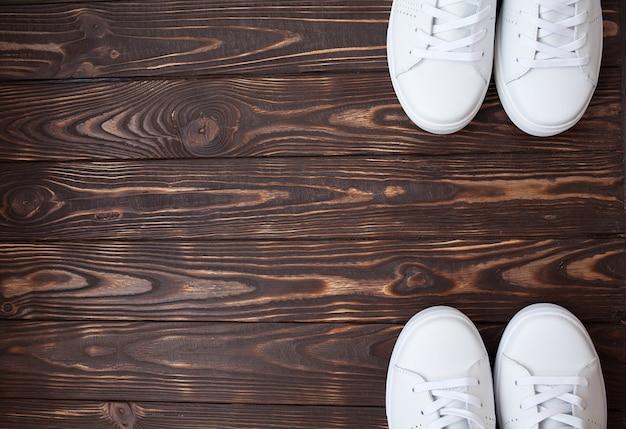 木製の白いキャンバスシューズのペア。茶色の背景に白のスニーカー。