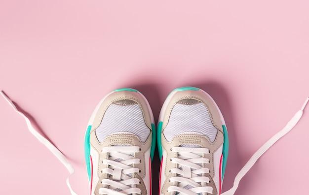 Пара белых кроссовок на розовой стене
