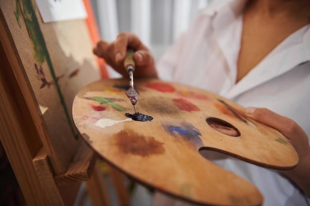 Мастихин с масляной краской на женской руке