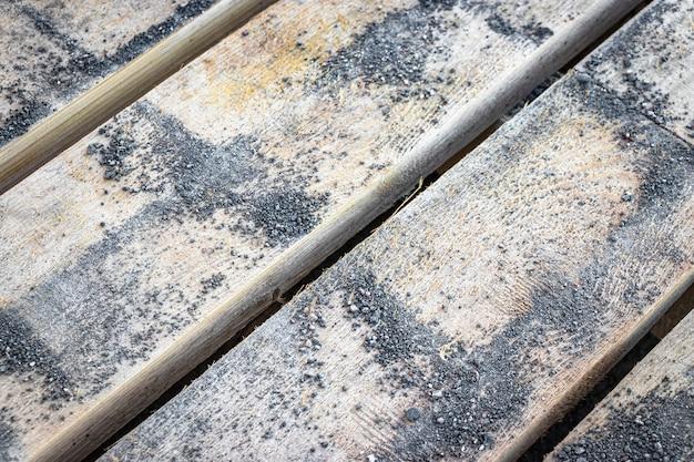 Поддон из тротуарной плитки, покрытой бетонной стружкой. фон из деревянных досок с мелкой бетонной стружкой.