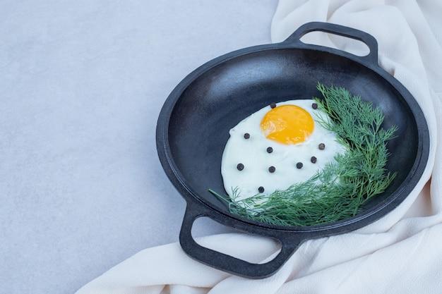白にコショウと緑のオムレツの鍋。