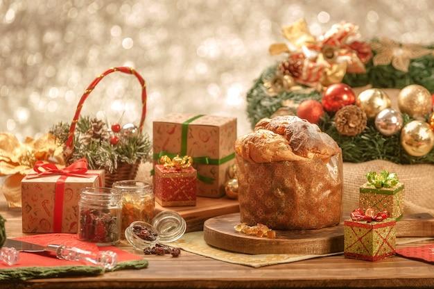 クリスマスの飾りと木製のまな板上のパネットーネと砂糖漬けのフルーツキューブ