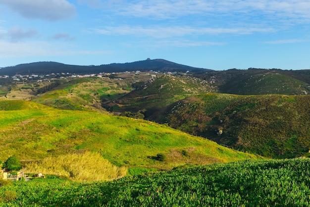 Панорама холмов, покрытых травой, и небольшой поселок у подножия гор.