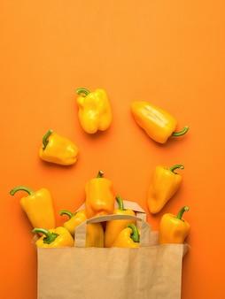 Бумажный пакет и разбросанные болгарские перцы на оранжевом фоне. вегетарианская пища. плоская планировка.