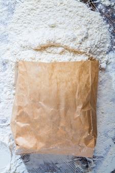 テーブルの上の小麦粉の紙袋、いくつかの白い小麦粉が袋からこぼれました