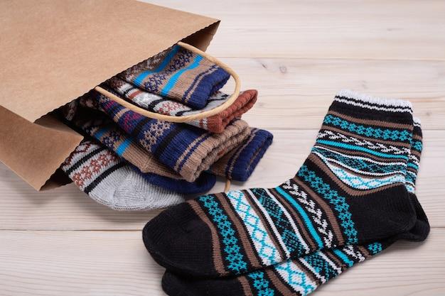 飾り付きの暖かい靴下のセットが入った紙袋