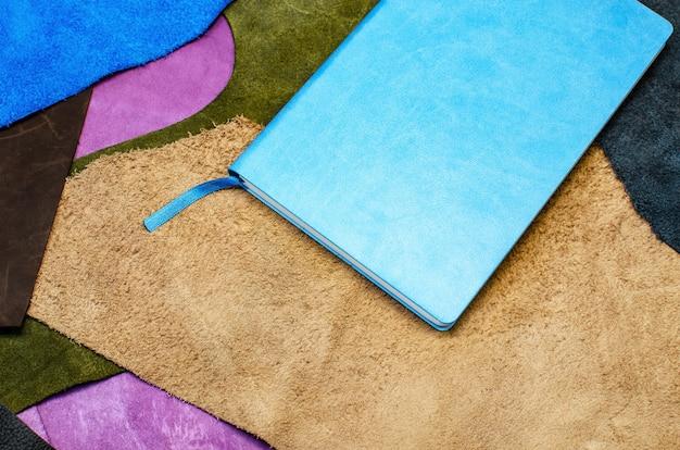 책갈피가 있는 파란색 가죽 커버의 종이 다이어리. 멀티 컬러 가죽 조각에.
