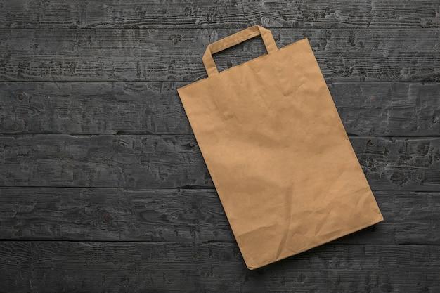 Бумажный упаковочный пакет на черном деревянном столе. плоская планировка.